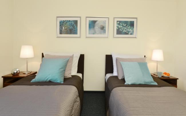 dwa łóżka z brązową narzutą Ikea i turkusowymi poduszkami