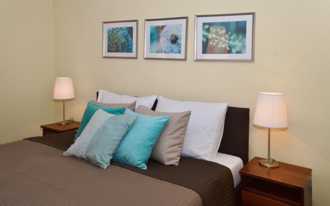 łóżko z brązową narzutą Ikea i turkusowymi poduszkami