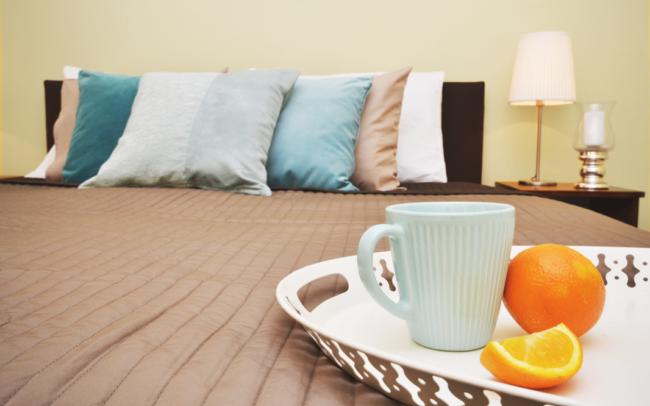 łóżko z brązową narzutą, turkusowymi poduszkami, błękitnym kubkiem i pomarańczami