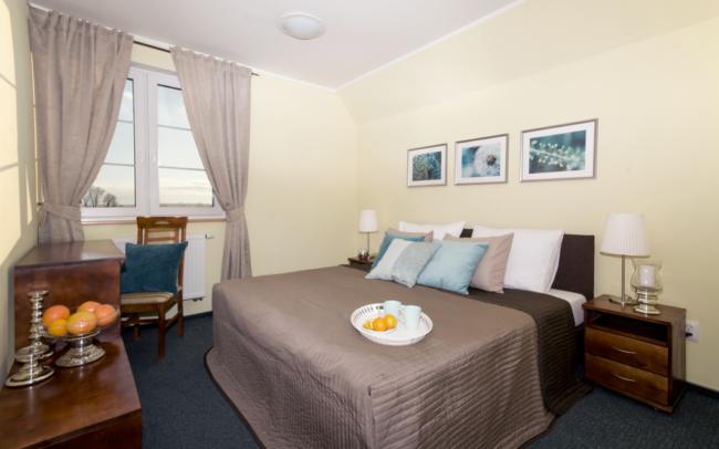 sypialna hotelowa z łóżkiem z brązową narzutą Ikea i turkusowymi poduszkami